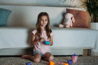 little kid pretending ti have tea party while sitting on floor at home