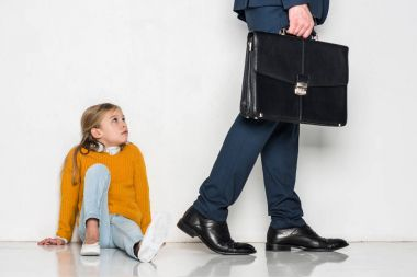 upset daughter looking at father in business suit walking away isolated on grey
