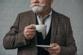 Fotografie cropped shot of senior man with cup of coffee