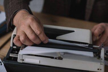cropped shot of writer loading paper into typewriter