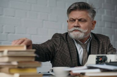 close-up shot of bearded senior writer at workplace taking book from stack