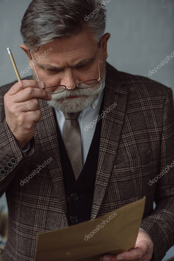 thoughtful senior man with pencil and sheet of paper