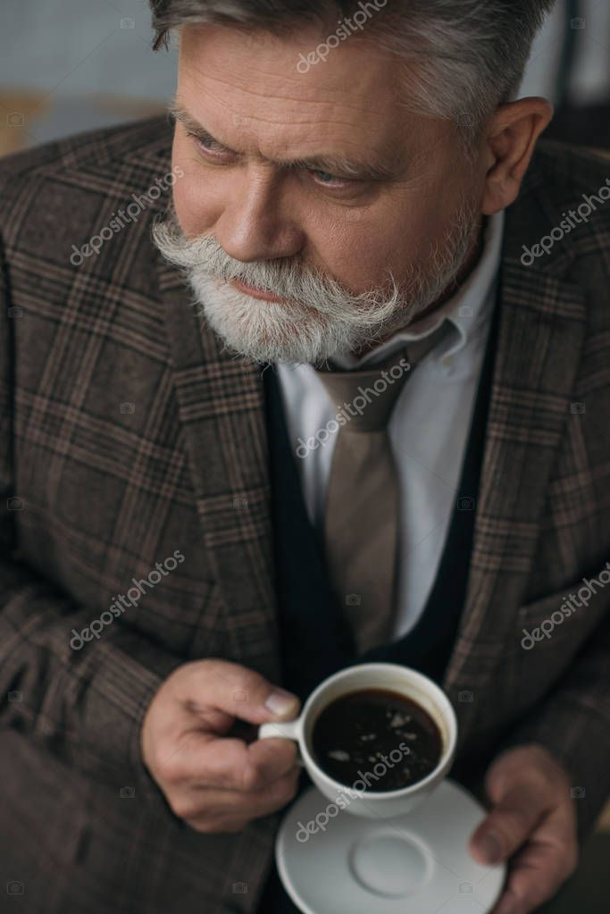 high angle view of senior man with cup of coffee