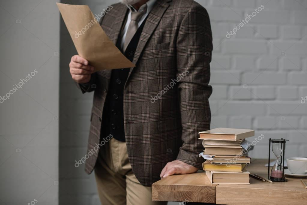 cropped shot of man reading letter while leaning at work desk