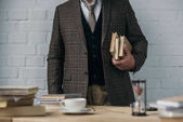 Photo cropped shot of man in tweed costume holding stack of books