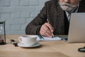 Schnappschuss eines älteren Schriftstellers, der mit Laptop arbeitet und Notizen in Notizbuch macht