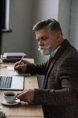 ernsthafte senior Schriftsteller arbeiten mit Laptop und Notizen im Notizbuch