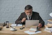 Nachdenklicher Senior-Autor arbeitet mit Laptop