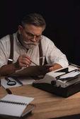 cílené senior spisovatel pracuje s rukopis izolované na černém pozadí
