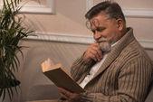 šťastný starší muž v svetru čtení knihy