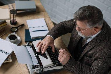 high angle view of senior writer working with typewriter