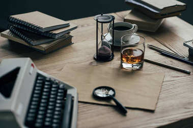 close-up shot of writer workplace with whiskey glass and typewriter