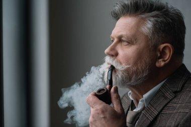 bearded senior man in tweed costume smoking pipe