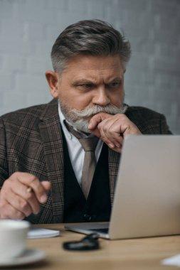 thoughtful senior man looking at laptop
