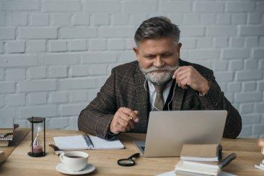 happy senior writer working with laptop