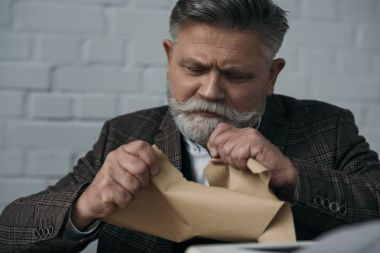 Close-up portrait of disappointed senior writer tearing his manuscript stock vector