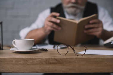 senior man reading book at work desk with cup of coffee and eyeglasses on foreground