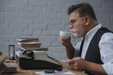 senior writer working with vintage typewriter and drinking coffee
