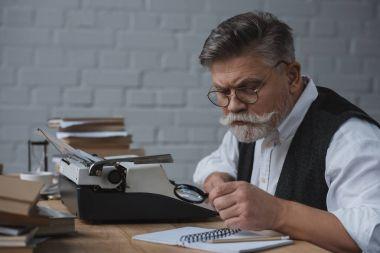 senior writer rewriting manuscript with typing machine