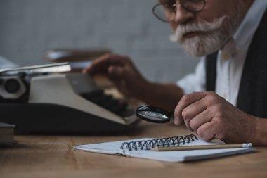 close-up shot of senior writer rewriting manuscript with typing machine