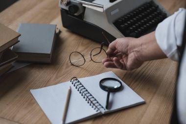 senior writer putting eyeglasses on work desk