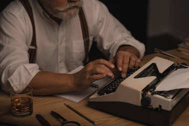 cropped shot of senior writer working with typewriter isolated on black