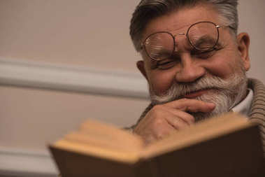 close-up portrait of senior man reading book