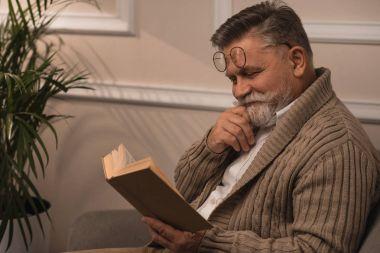 Happy senior man in sweater reading book stock vector