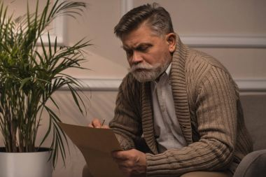thoughtful senior man in sweater writing letter while sitting in armchair