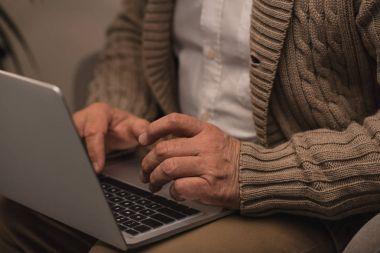 cropped shot of senior man using laptop