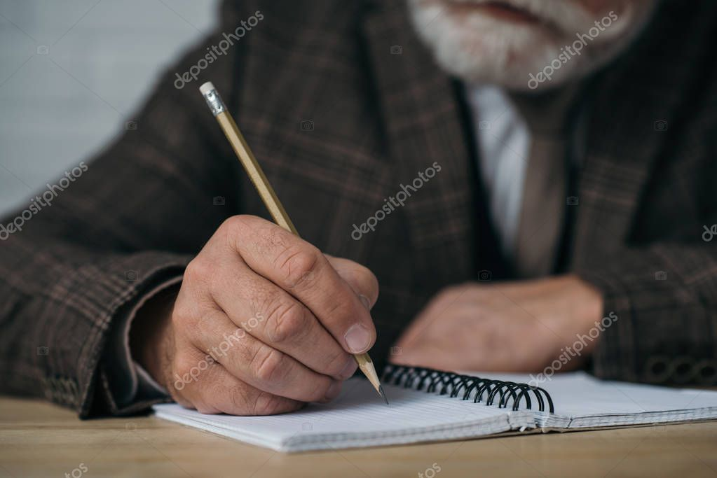 close-up shot of senior man writing in notebook with pencil