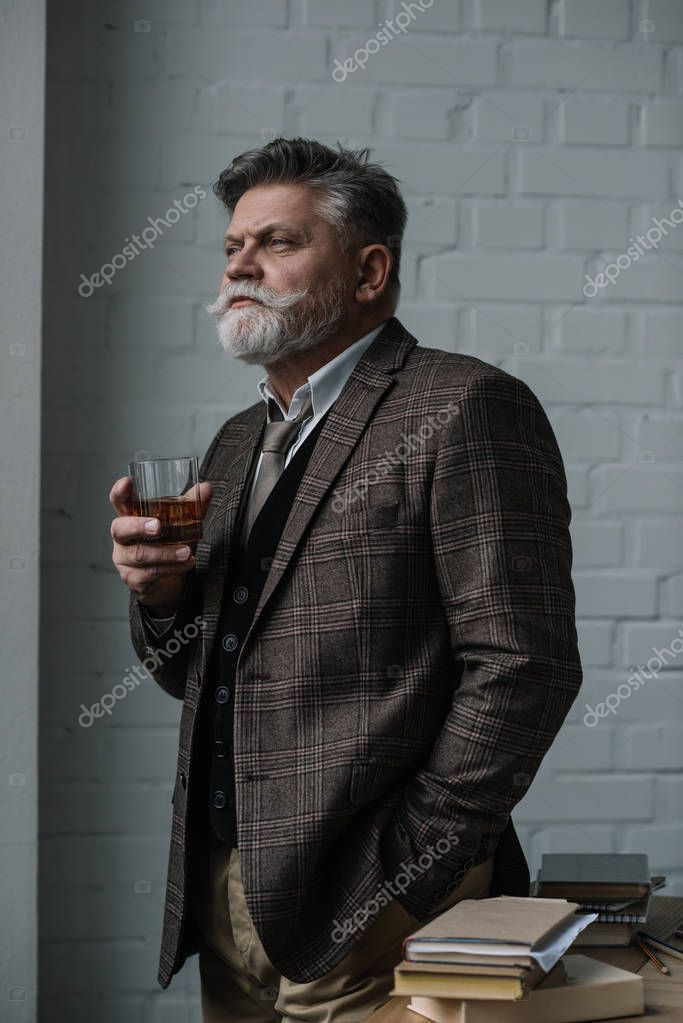 senior man in tweed suit with glass of whiskey looking away