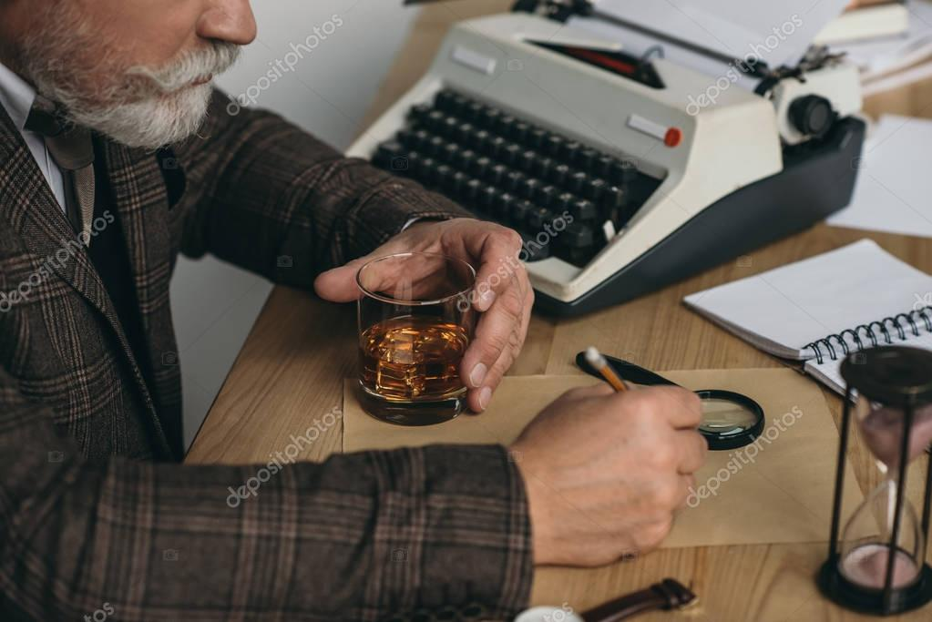cropped shot of senior writer working on manuscript and holding glass of whiskey