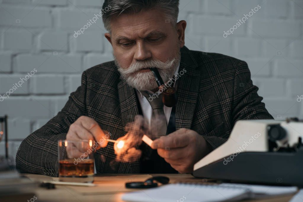 bearded senior writer with burning match smoking pipe at workplace