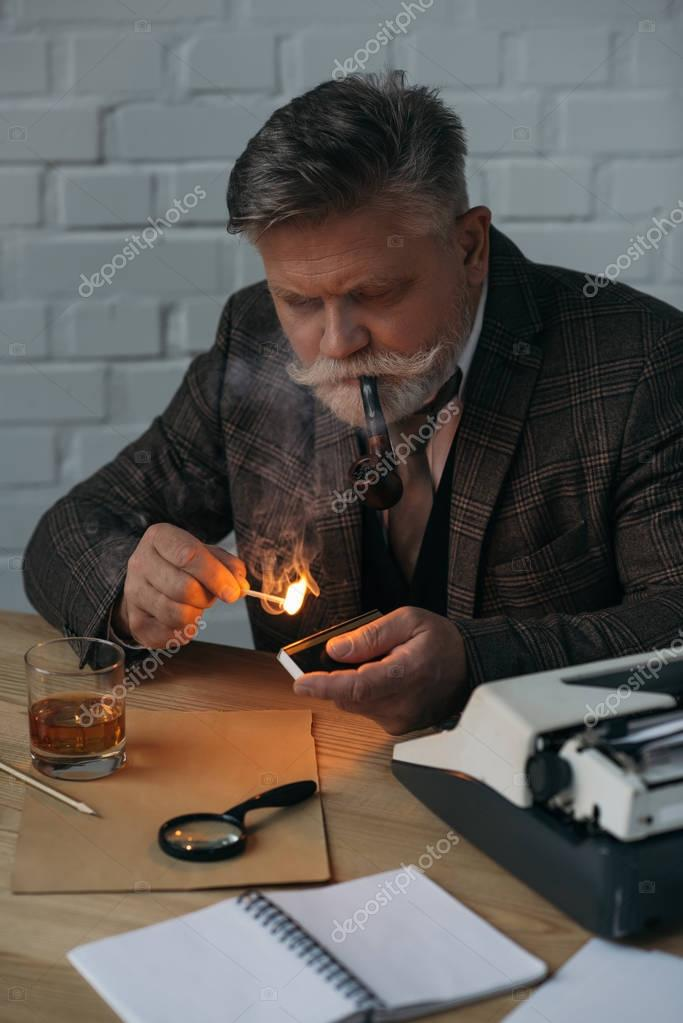senior writer with burning match smoking pipe at workplace