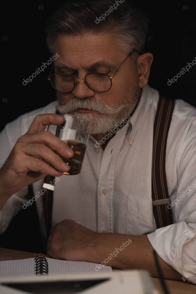handsome senior man drinking whiskey on black