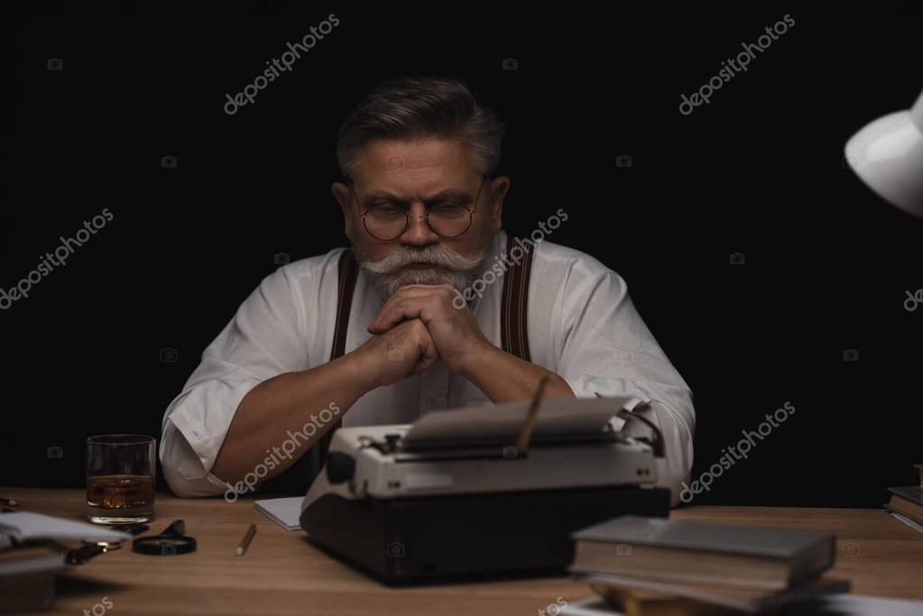 thoughtful senior writer sitting at workplace isolated on black