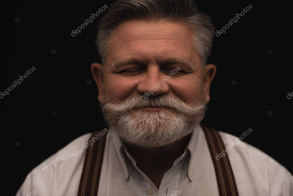 smiling bearded senior man isolated on black