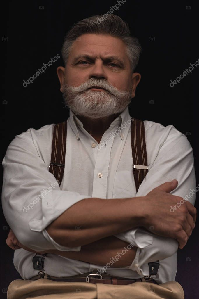 serious senior man with crossed arms isolated on black