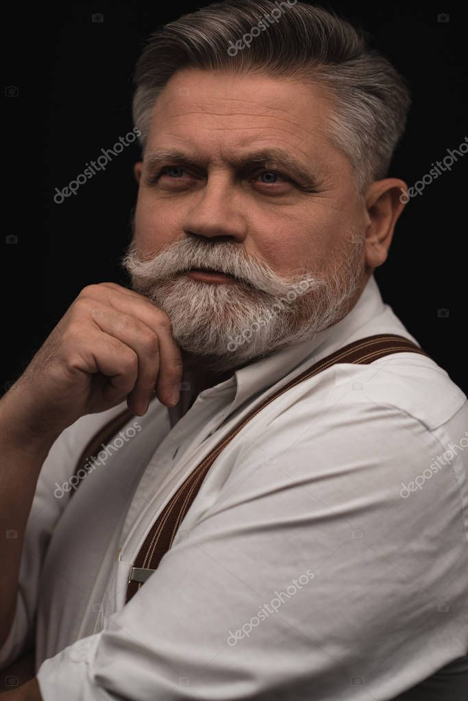 thoughtful senior man in white shirt with suspenders isolated on black