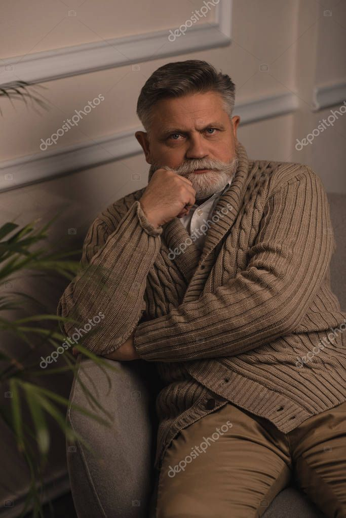 serious senior man sitting in armchair and looking at camera