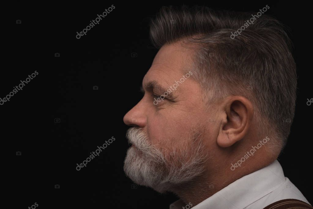 side view of senior man with stylish beard isolated on black