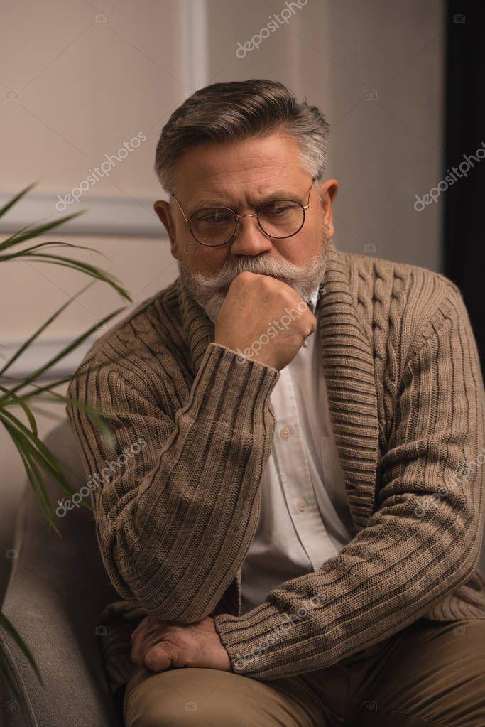 thoughtful senior man sitting in armchair