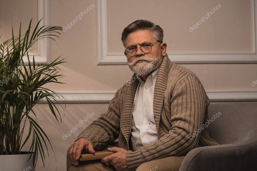 senior man sitting in cozy armchair and looking at camera