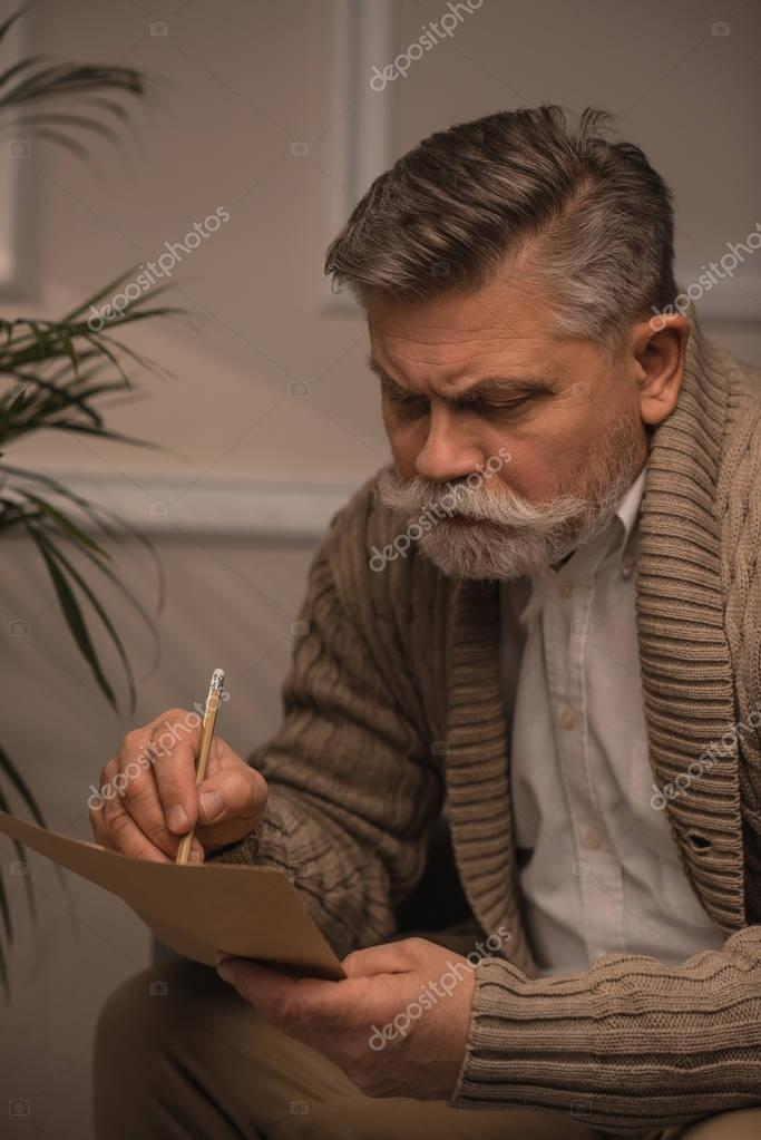 thoughtful senior man in sweater writing letter