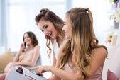 Fotografie krásné šťastné mladé ženy společné čtení módní časopis na pyžama párty