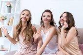 belle giovani donne in pigiama che tiene i capelli come baffi e sorride alla macchina fotografica
