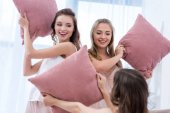 Fotografie beautiful happy girlfriends in pajamas fighting with pillows
