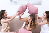 Fotografie attractive happy girlfriends in pajamas fighting with pillows at home