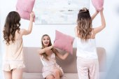 Fotografie beautiful young women in pajamas fighting with pillows at home